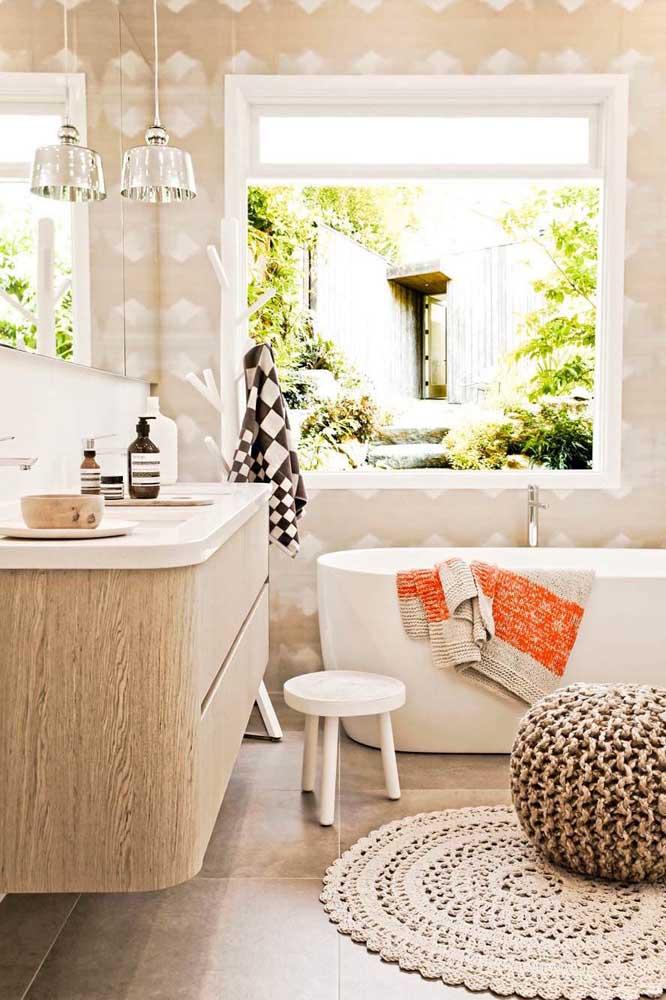 Esse banheiro super acolhedor traz uma janela grande que permite contemplar toda a área externa da casa