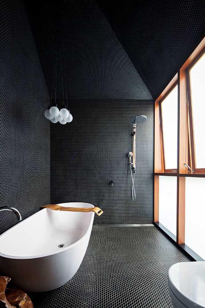 O banheiro de revestimento preto precisa de muita luz para não ficar sobrecarregado. Ainda bem que as janelas de madeira resolvem esse impasse