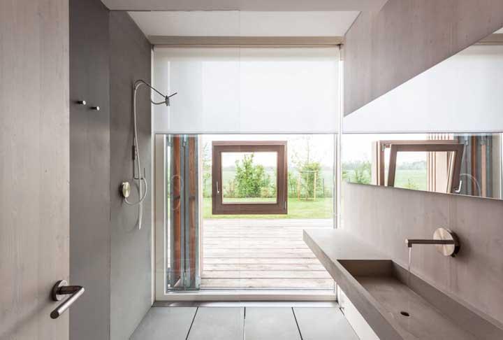 A parede de vidro traz uma janela basculante de madeira bem no centro