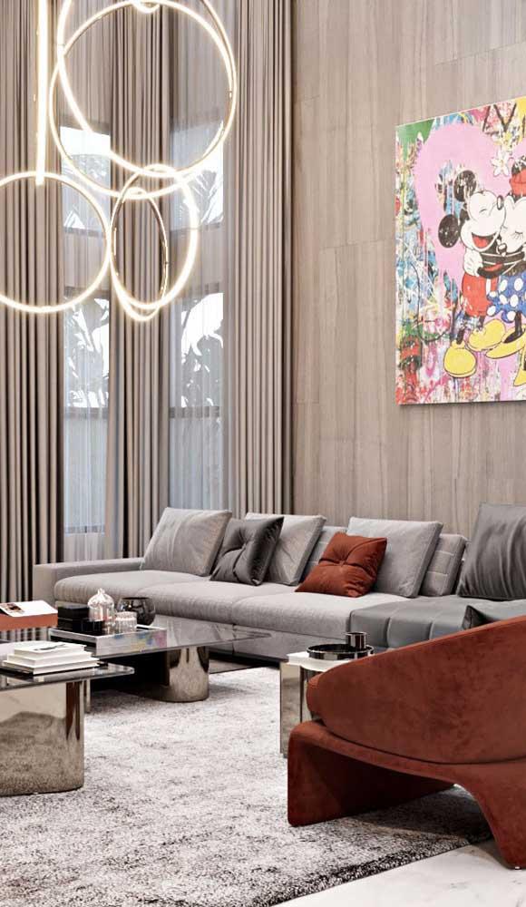 Sala de estar com pé direito alto e luminária pendente de tamanho grande