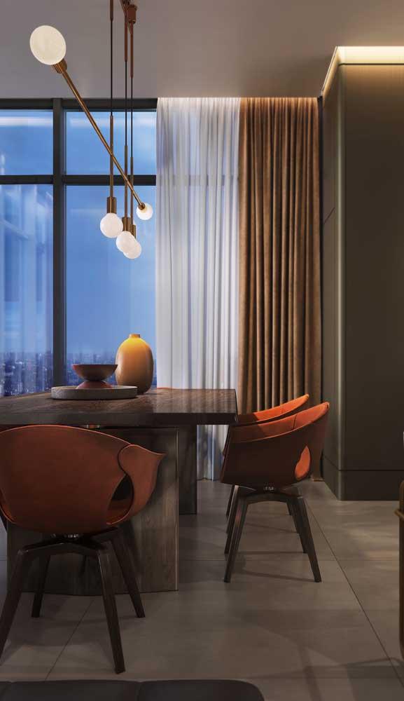 Nessa sala de jantar, a luminária pendente é o grande destaque