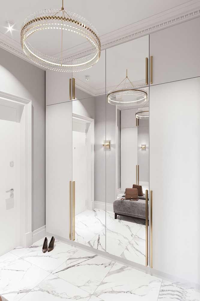 Super elegante, esse quarto com piso de mármore e detalhes em dourado apostou em um guarda-roupa com espelho em apenas duas portas