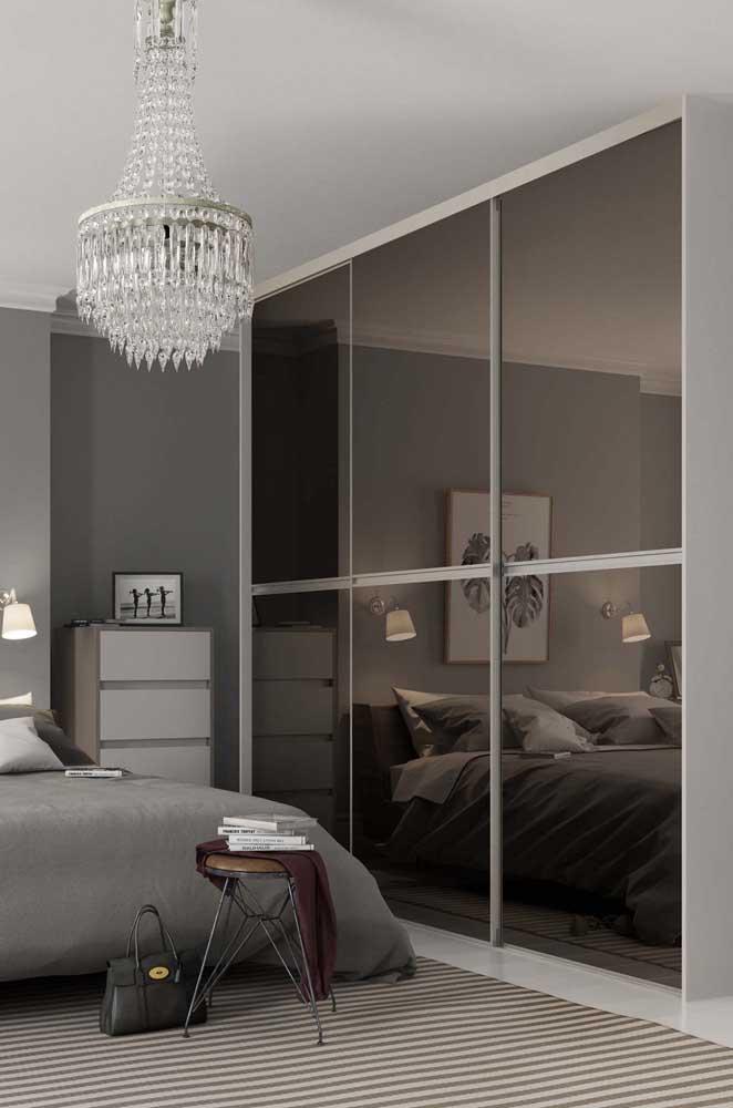 O espelho escuro do guarda-roupa se harmoniza muito bem com a paleta de cores neutras do quarto