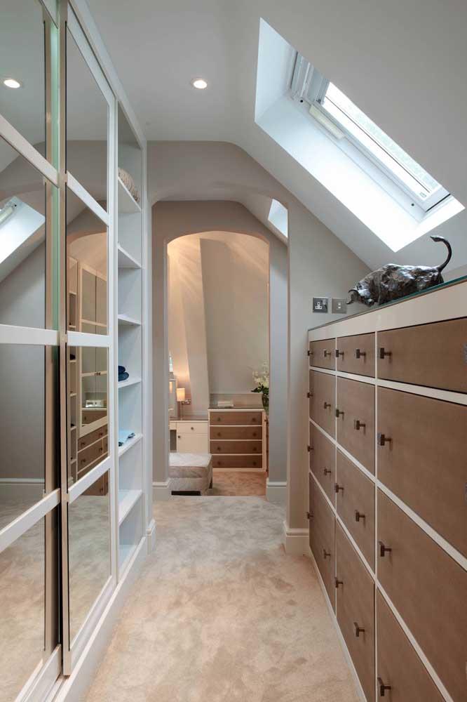 Um closet com iluminação valorizada pelos espelhos do guarda roupa