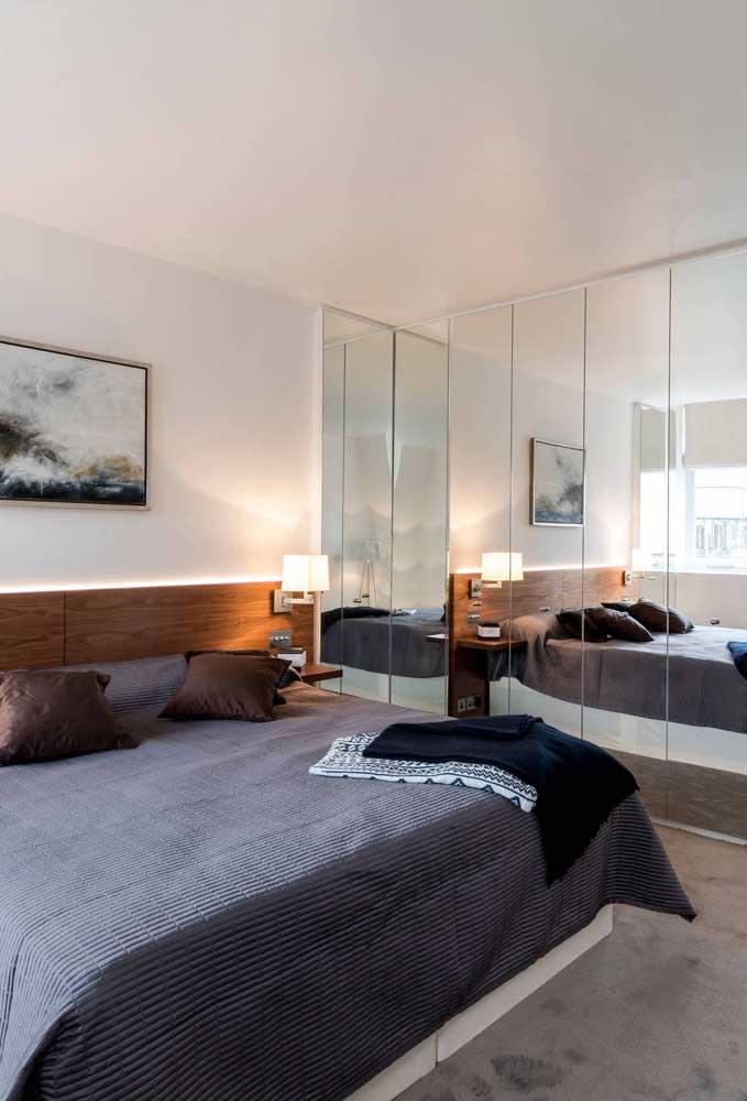 O quarto ganha espaço visualmente com o guarda-roupa com espelho 4 portas. Repare no outro espelho na parede da cama que reforça ainda mais a sensação de amplitude no quarto