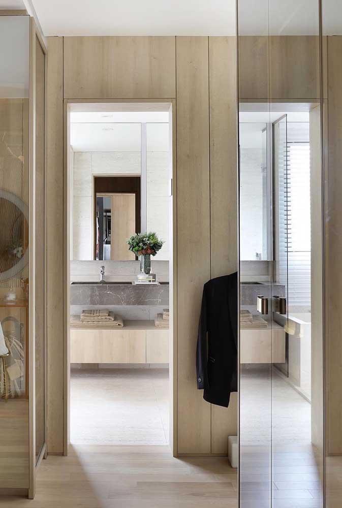 O quarto amadeirado ganhou modernidade com o guarda-roupa com espelho
