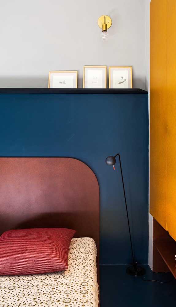 Para criar contraste nada melhor do que uma cabeceira marsala sobre uma parede azul petróleo