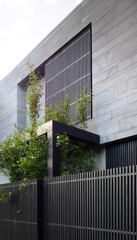 A madeira escura usada no portão e no revestimento da fachada traz modernidade e elegância para casa