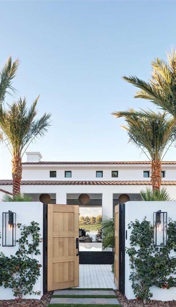 Portão de madeira de abrir com duas folhas completando o visual da casa