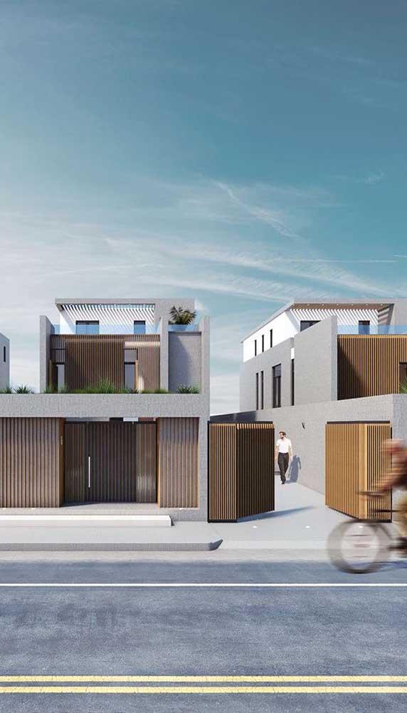 Portão de madeira automático combinando com os demais elementos em madeira da fachada