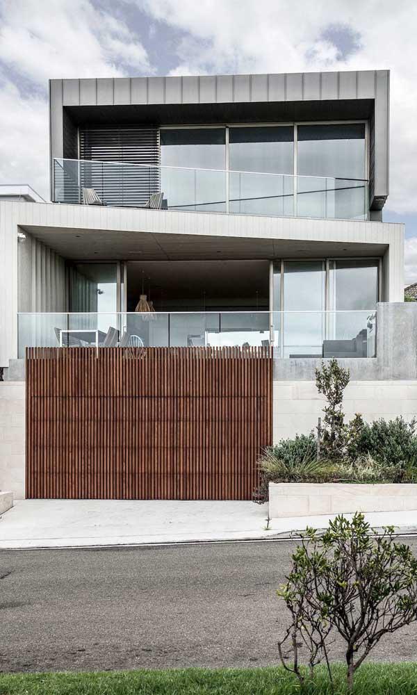 O lindo contraste entre o rústico do portão de madeira com o moderno das paredes de concreto