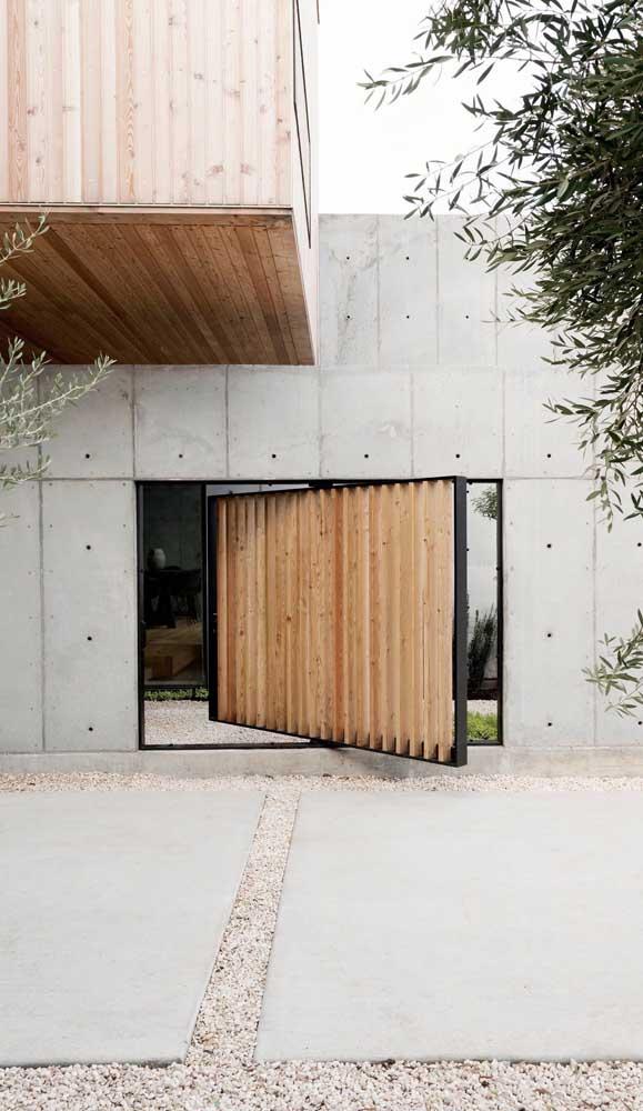 Super moderno, esse portão de madeira pivotante se destaca na parede de concreto aparente