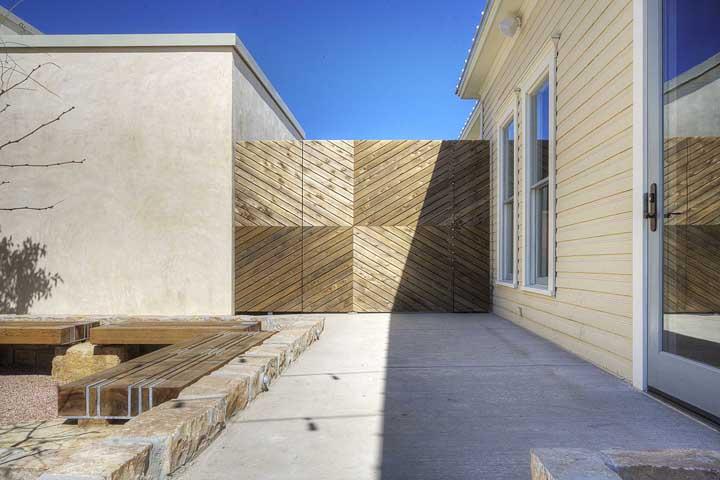 Portão de madeira na cor da casa (que também é de madeira)