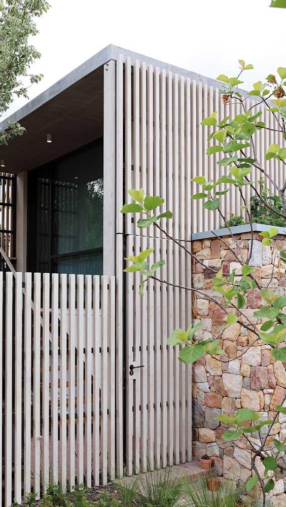 Aqui, a madeira de eucalipto foi a escolhida para fazer o portão e parte do muro