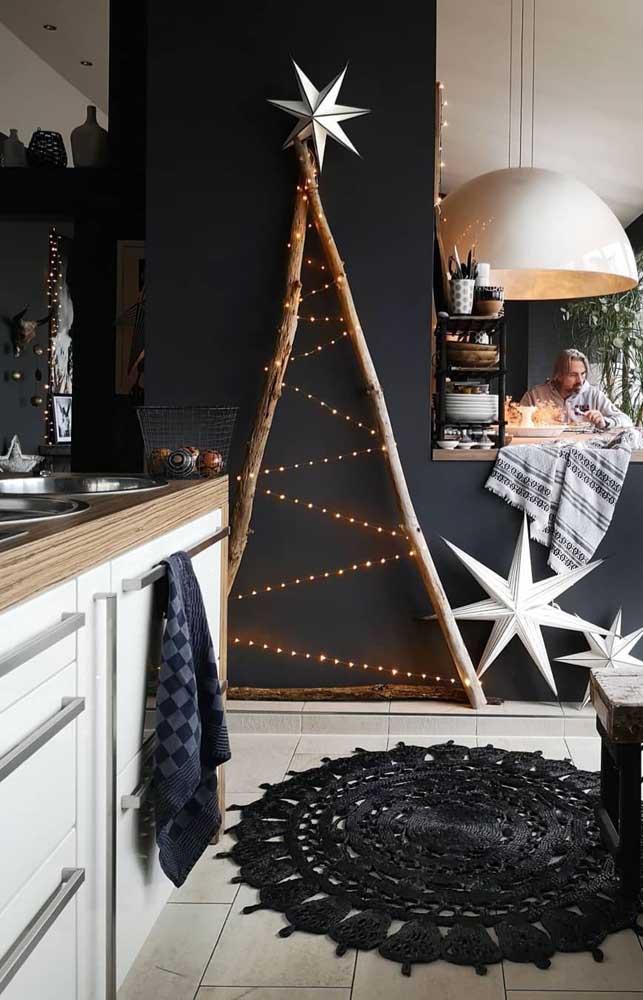 A estrela dourada finaliza essa árvore de natal de parede feita com galhos secos