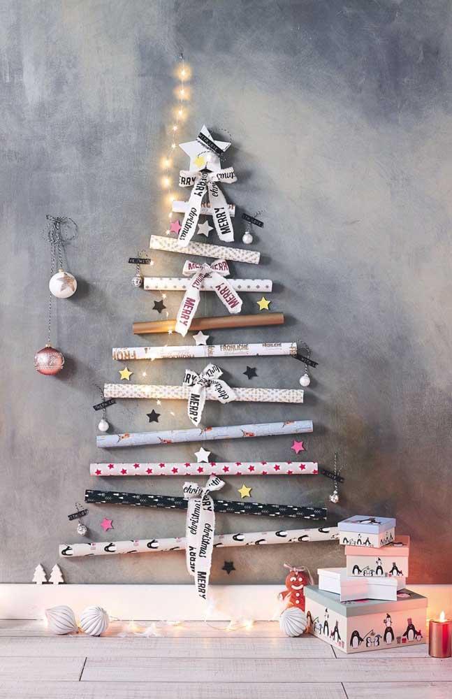 Essa ideia é bem criativa: Árvore de natal de parede feita com rolos de papel de presente