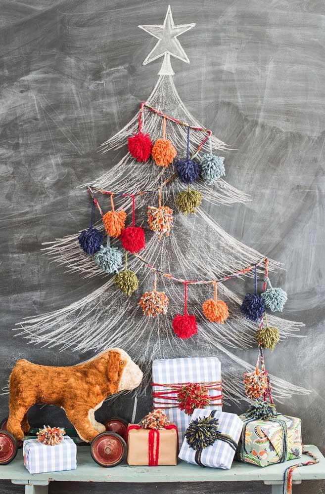 Aqui, a árvore de natal desenhada na parede lousa foi decorada com pompons de lã