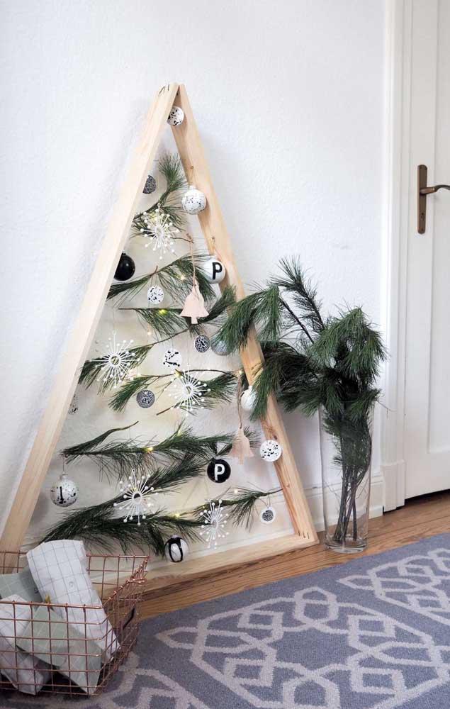 Um nicho triangular dá vida a essa árvore de natal. Quando a festa acabar, você ainda pode reaproveitar a estrutura na decoração