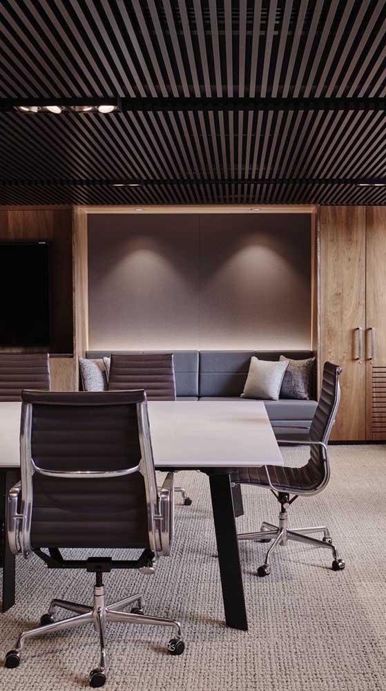 Mesa de reuniões rodeada por cadeiras giratórias do tipo executiva