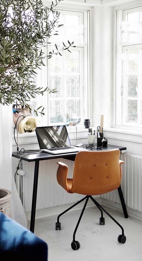 Esse home office arrasou na escolha da cadeira giratória caramelo em meio a decoração preto e branco