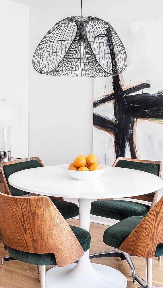 Conjunto de mesa com cadeiras giratórias. Repare que o modelo mescla madeira com estofado de veludo e base metálica