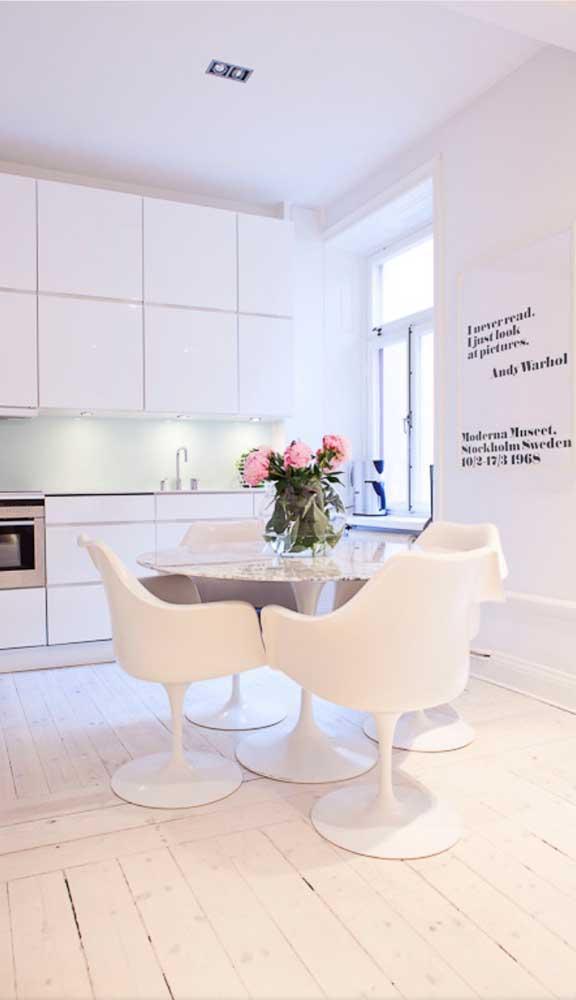 Essa sala de jantar integrada à cozinha aproveitou o amplo espaço para apostar em cadeiras giratórias junto à mesa de jantar