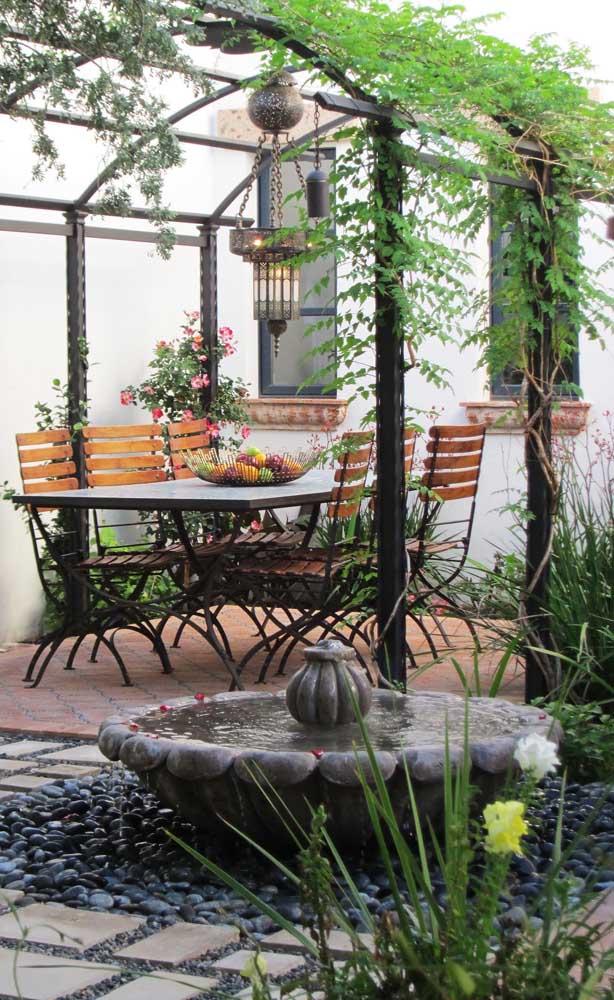 Caramanchão de ferro para a área externa da casa. Repare que a mesa e as cadeiras acompanham o estilo da estrutura