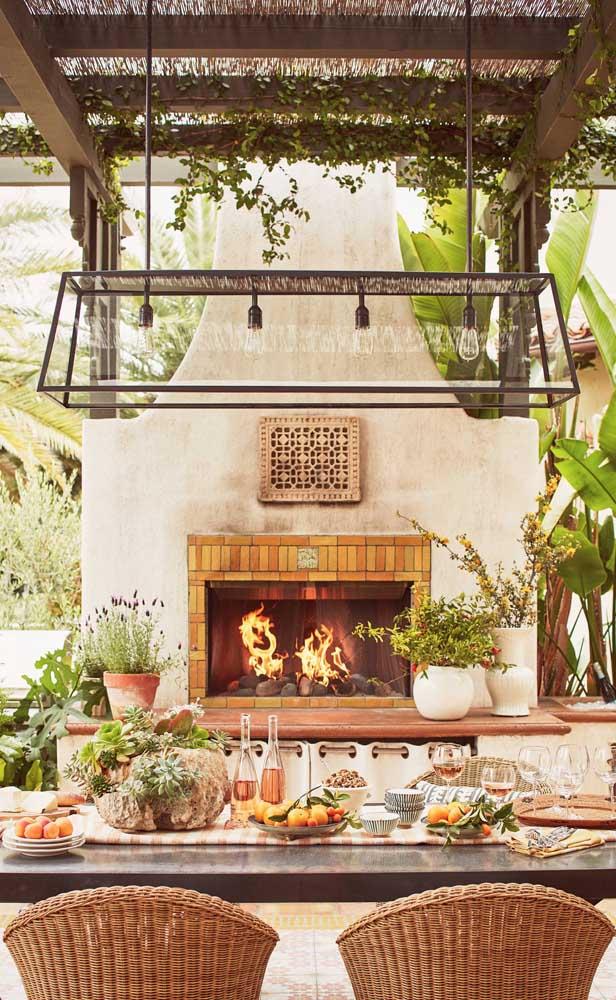 Terraço gourmet construído a sombra de um caramanchão de madeira. Repare que a estrutura possui um pé direito alto para acomodar a todos com conforto