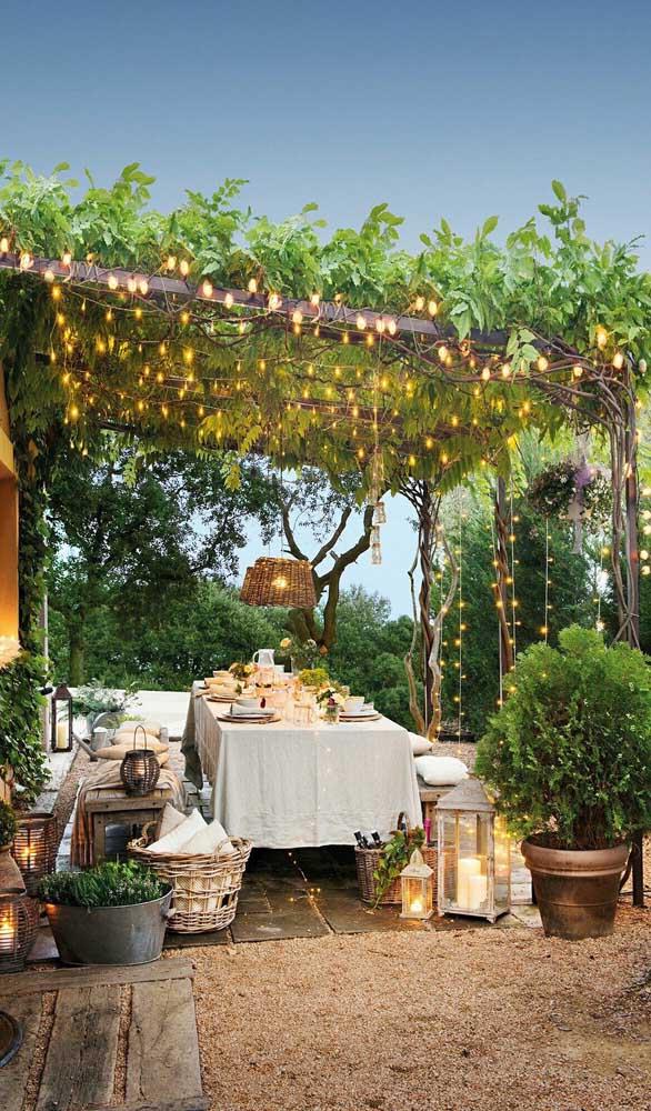 Varanda gourmet embaixo do caramanchão. As luzes conferem um clima ainda mais especial para a estrutura