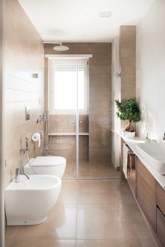 O banheiro longo e estreito apostou em um conjunto de vaso com bidê na cor branca