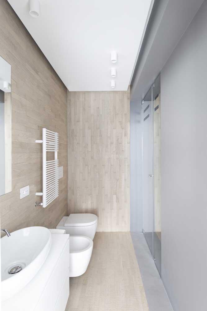 Nesse banheiro pequeno, estilo corredor, o lavatório, o vaso sanitário e o bidê foram instalados na mesma parede para economizar espaço