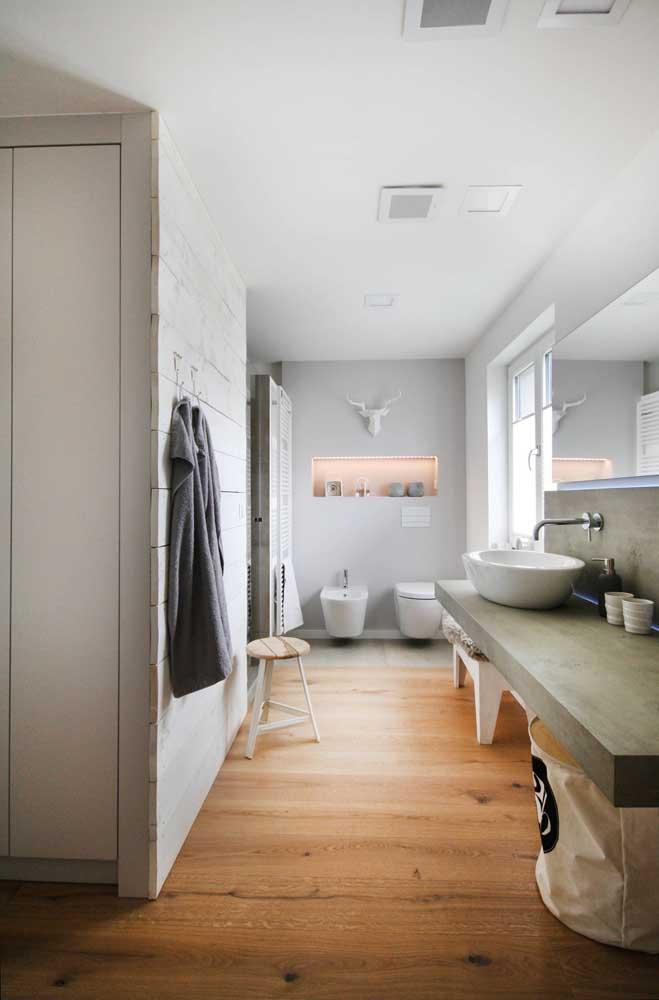 Nesse amplo banheiro, o bidê e o vaso sanitário ocupam a parede aos fundos