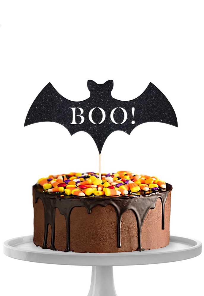 Bolo simples de chocolate com cobertura de doces. Para finalizar um morcego de papel fixado no topo