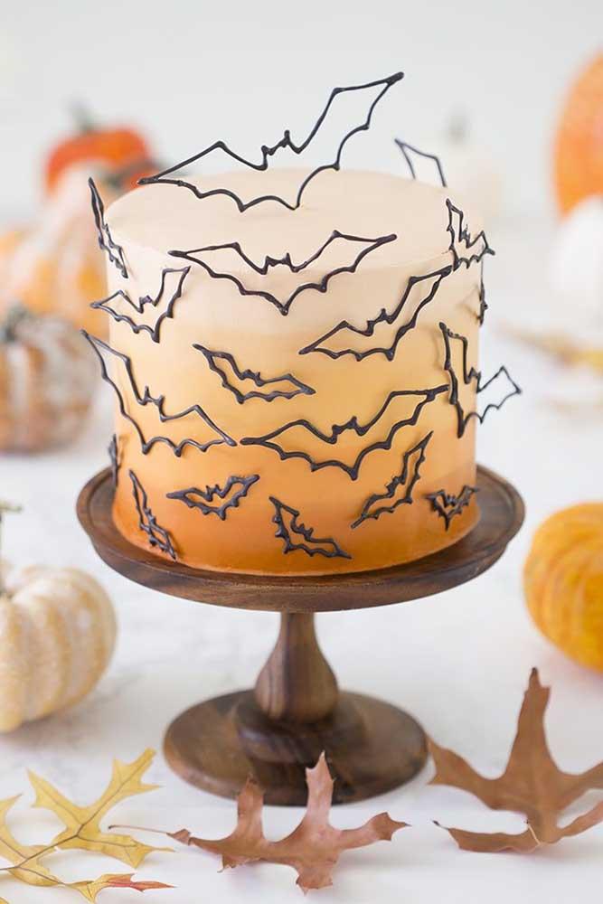 Bolo de Halloween decorado com pasta americana em degradê de tons de laranja. A decoração fica por conta dos morceguinhos voando ao redor do bolo