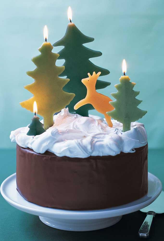 Velas com tema de natal decoram o topo desse bolo pequeno e simples