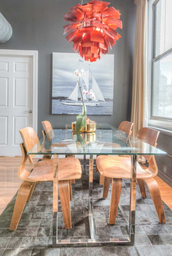 Aqui, a mesa moderna retangular conta com a decoração glamorosa do lustre vermelho