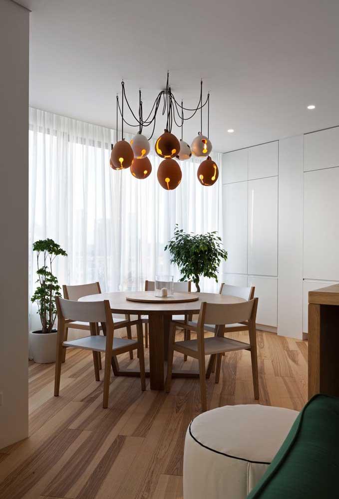 """Nessa sala de jantar, a mesa redonda ganhou um lustre super moderno onde cada """"braço"""" possui uma cúpula"""