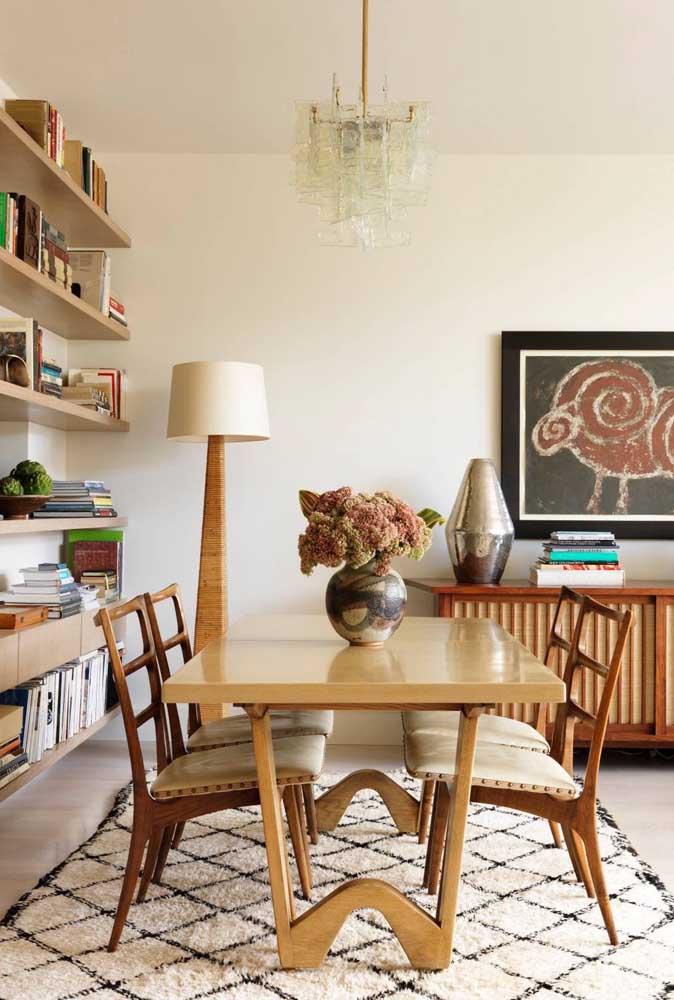 Sala de jantar com lustre de vidro criando contraste com as peças de madeira