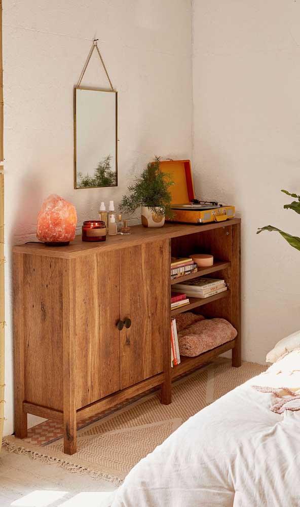 Uma cômoda de madeira do tamanho e no formato das necessidades dos moradores. Repare que o móvel possui gavetas e um nicho aberto