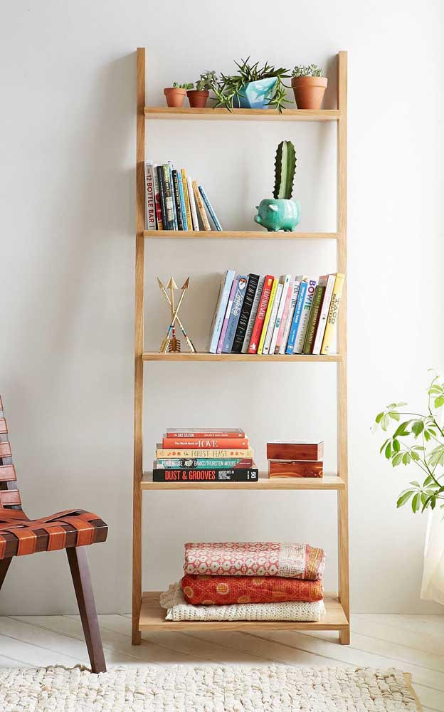 Estante escada para acomodar os livros da sala de estar. Plantas e algumas mantas também são bem vindas