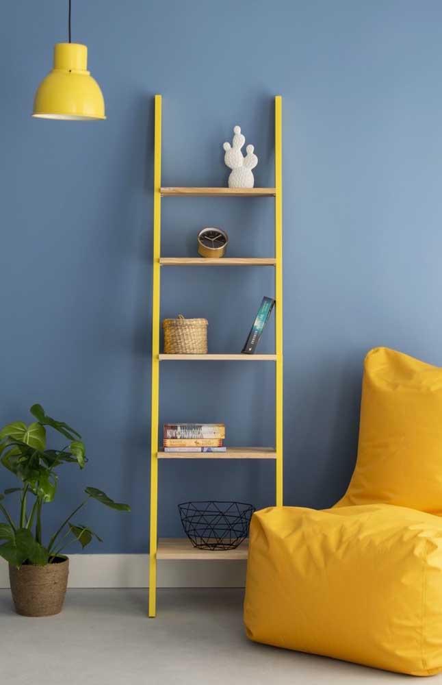 Estante escada amarela para contrastar com a parede azul