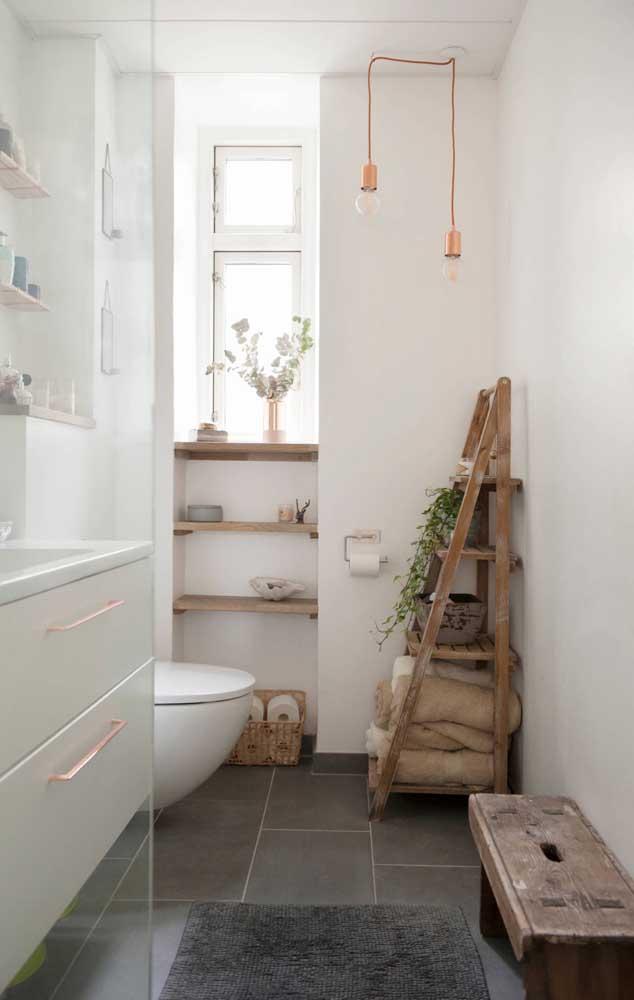 Já nesse outro banheiro, a estante escada rústica guarda toalhas e acomoda as plantas