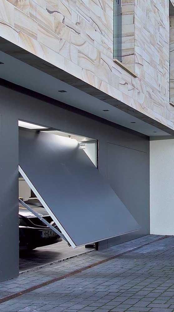Portão basculante todo fechado em tom de cinza para combinar com o restante da fachada moderna