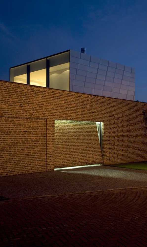 Portão basculante camuflado no muro da fachada