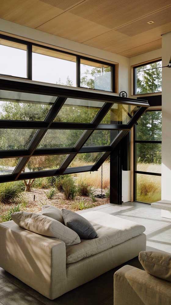 As folhas de vidro do portão basculante enchem a casa de luz e, ainda, permitem contemplar a paisagem, como se fosse uma grande janela