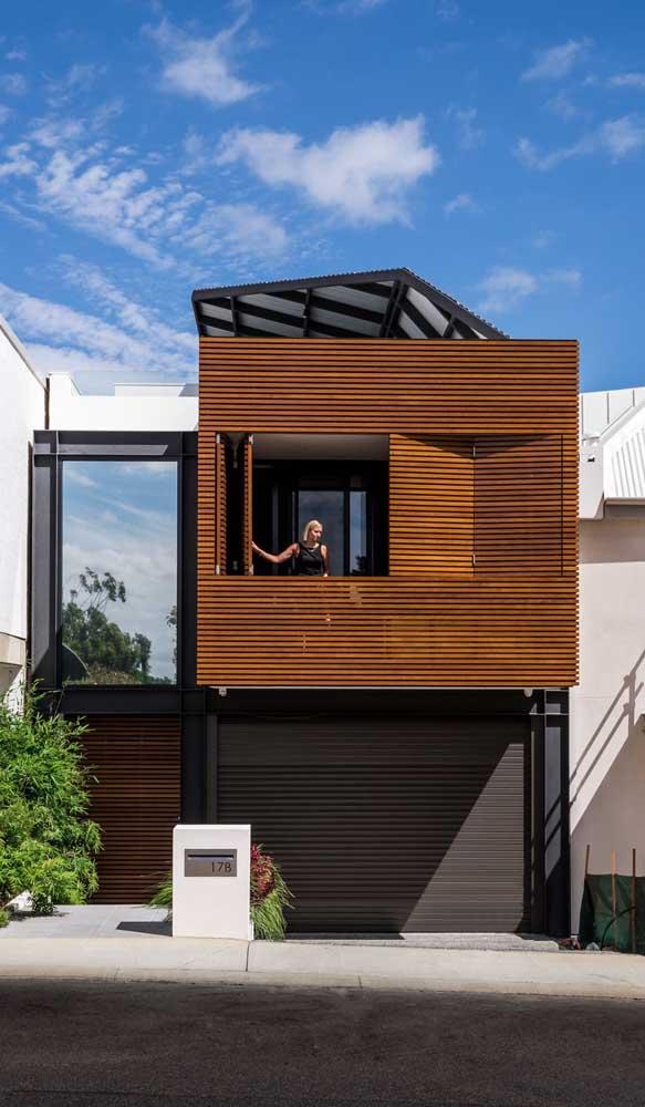 Portão basculante em aço combinando com os demais elementos da fachada