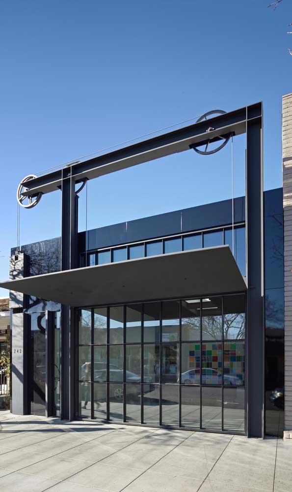 O sistema de roldanas aparente garantiu um charme super especial para esse portão basculante, evidenciando a estética moderna da fachada