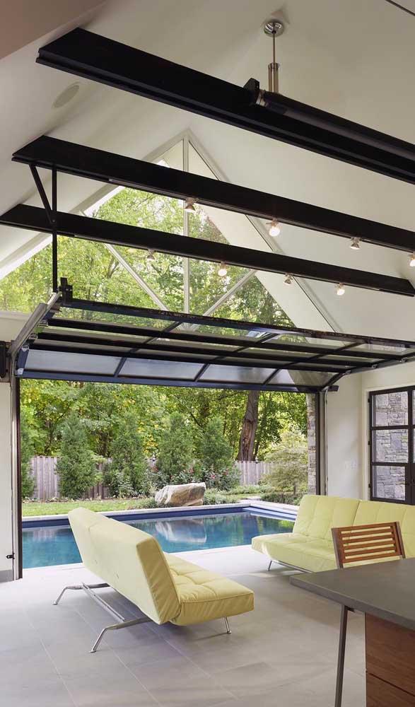 Entre a sala e a piscina um sofisticado portão basculante de vidro e alumínio