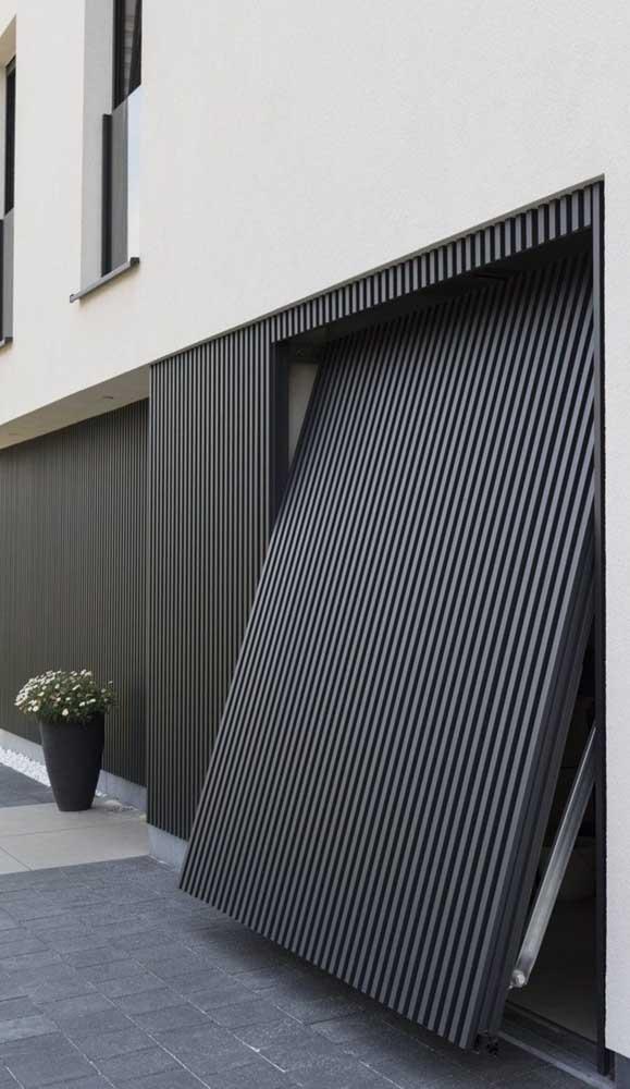 A fachada elegante e neutra apostou em um portão basculante preto