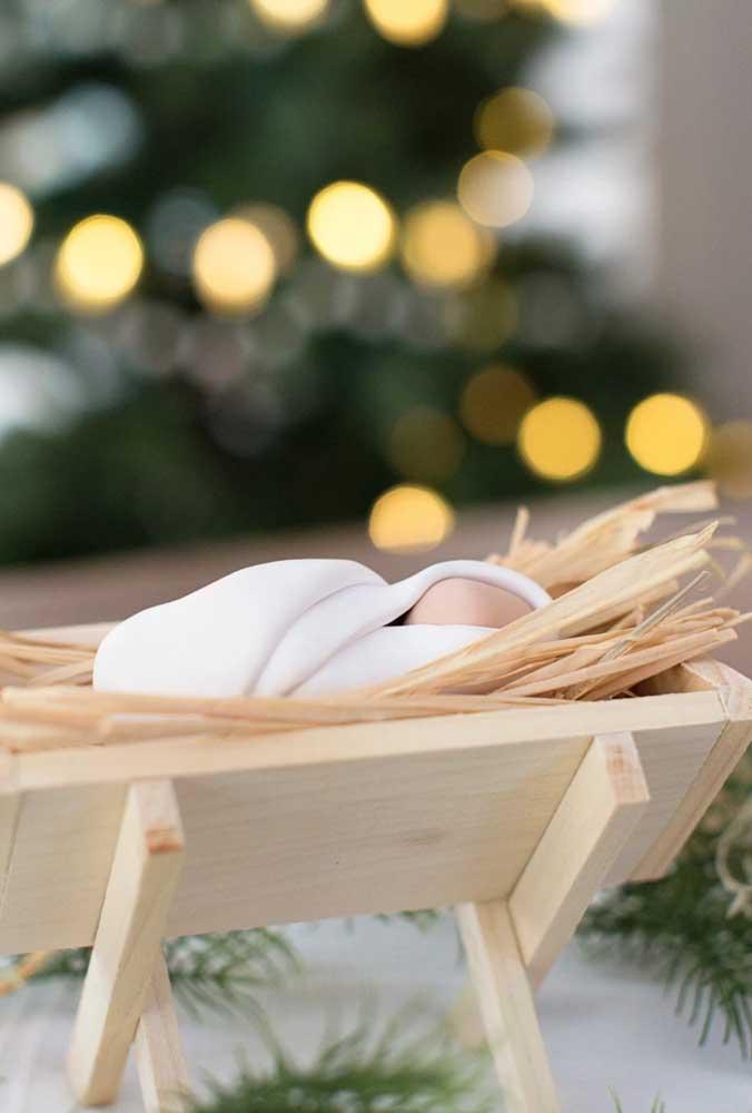 O menino Jesus de biscuit se destaca dentro da manjedoura de madeira